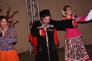 Казак в черной черкесске и кубанке и две казачки на сцене