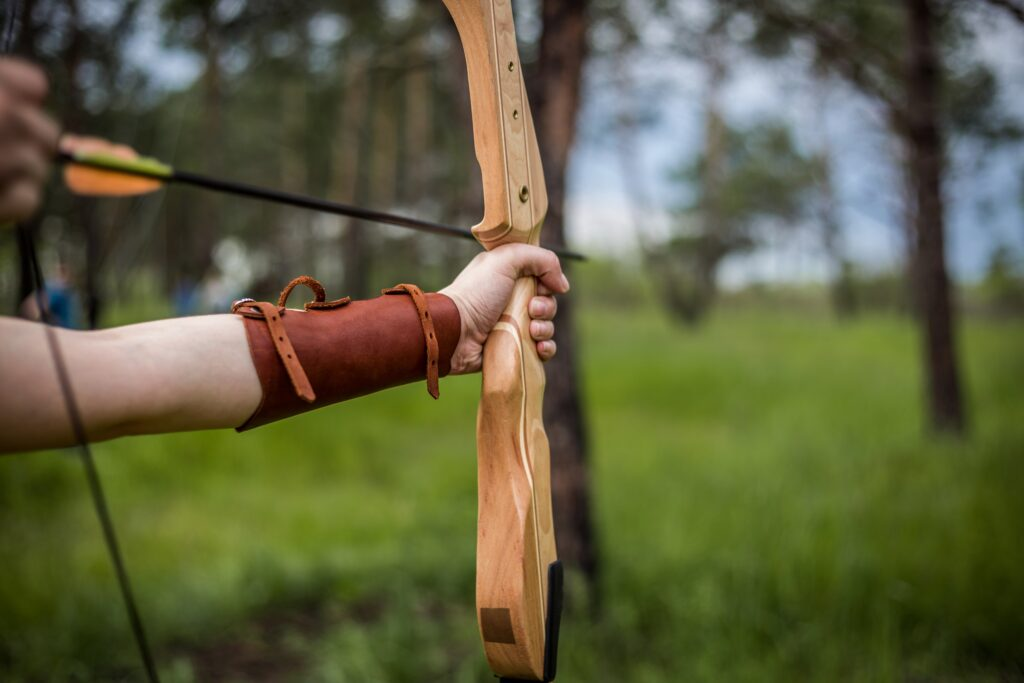 hand forest leather game brown weapon bracelet arrow shooting sports day archery green background bow and arrow cold weapon longbow 1194132 1